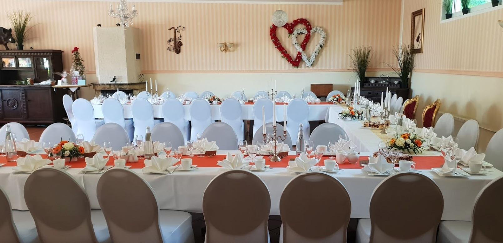 Hochzeitstisch eingedeckt mit weißen Stuhlhussen